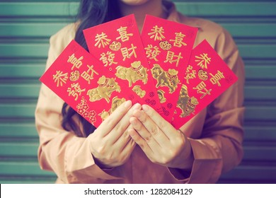 Year of the Pig or Chinese Lunar New Year celebrations theme woman holding four red envelopes with pigs image and blessing word. The Chinese words Gong Xi Fa Cai means wishing you enlarge your wealth.