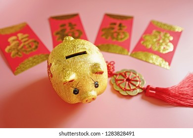 Year of the Pig, Chinese Lunar New Year celebrations theme golden piggy bank, red envelope with blessing word means happiness or good fortune, hanging decoration on pink background. (selective focus)