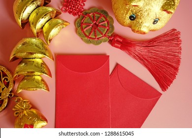 Year of the Pig Chinese Lunar New Year celebrations theme blank red envelopes, golden piggy bank, traditional Chinese ancient gold bullion nugget flat lay on pink background / top view, space for text