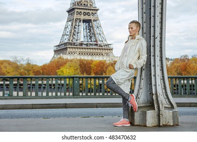 Year round fit & hip in Paris. Full length portrait of young healthy woman on Pont de Bir-Hakeim bridge in Paris looking into the distance