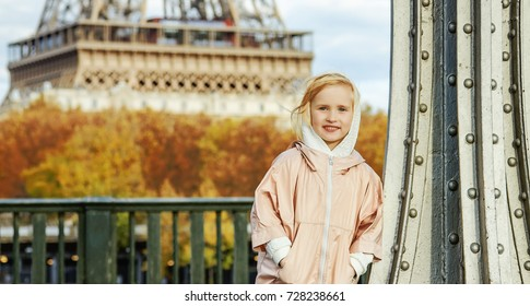 Year round fit & hip in Paris. Full length portrait of happy active girl in sport style clothes standing on Pont de Bir-Hakeim bridge in Paris