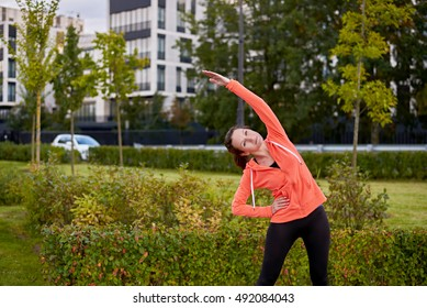 Yearly morning trainig in the city. Fitness girl making stretching exercises to prepair to run. Health morning concept.