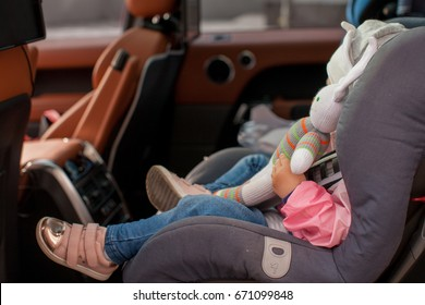Year-old Baby Buckled into her Car seat, Girl Travels in Car with Parents looking out the Window at sunset - Image