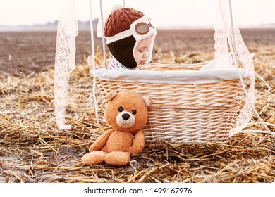 Year-old boy pilot in basket with yellow ball at sunset. Toddler and teddy bear friend.