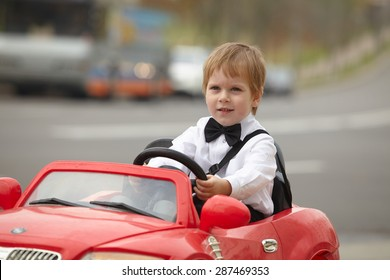 year-old boy in a white shirt in a red toy car in the street