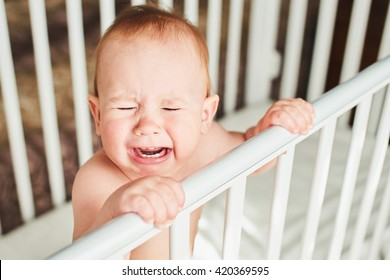 A year-old child is crying in the crib and holds onto the side of the bed