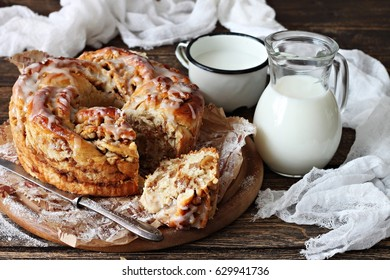 Yeast cake with nuts , sugar icing on top and milk bottle