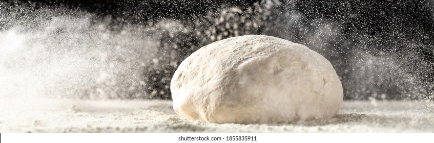 yeast dough for bread or pizza on a floured surface, with flour splash. Cooking bread. Kneading the Dough. Long banner format