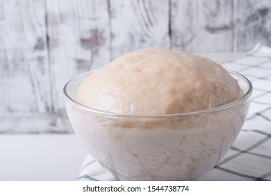 Yeast dough in a glass bowl ready to be formed into bakery products against white background