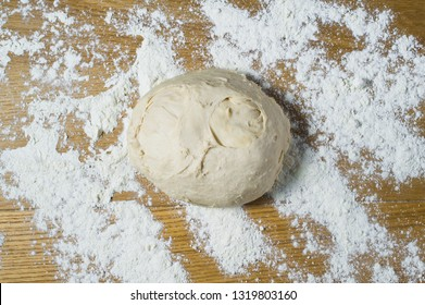 Yeast dough on a wooden table sprinkled . Top view, wooden background, space for text