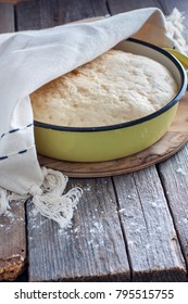 Yeast dough raw in a bowl on a wooden table. Country style, selective focus
