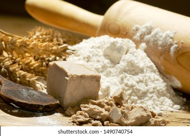 yeast with wheat flour, wheat ears and rolling pin