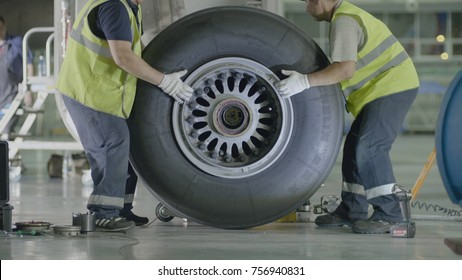 Yekaterinburg, Russia - August 2017: Passenger airplane maintenance personnel working on aircraft main landing gear repair. Engine and chassis of the passenger airplane under heavy maintenance