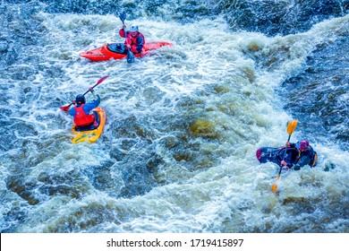 Yekaterinburg, Russia - June 8, 2019: Extreme whitewater rafting trip. A group of people (team) in kayaks practise traversing the water rapids. Kayaker paddling on the mountain river. Kayaking concept