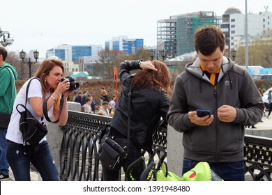 Yekaterinburg, Russia - May 7, 2019: The girl poses for the photographer on the street. Embankment of the river Iset of the city of Ekaterinburg