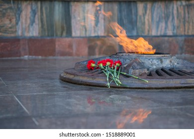 Yelabuga, Russia, September 8, 2019: memorial complex with eternal flame in honor of the memory of those killed in world war II. Near the eternal flame are red carnations. Copy space.