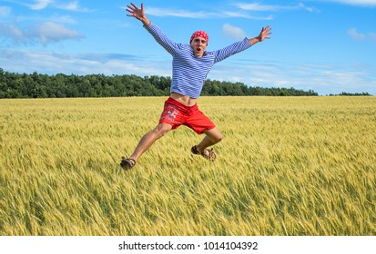 Yelets, Russia, July 2017:A cheerful man in a vest jumps high over a field of wheat
