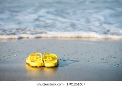 Yelllow flipflop shoes on beach with motion wave in Ao Nang, Krabi, Thailand. sandals on sand for fun holiday travel on summertime. Summer vacation vibes.