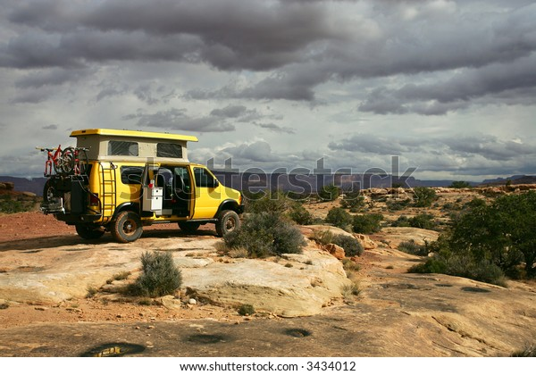 Yellow 4x4 van off-roading in Utah, North America with Island in the Sky on background