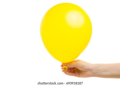 Yellow air balloon in a female hand on a white background isolation