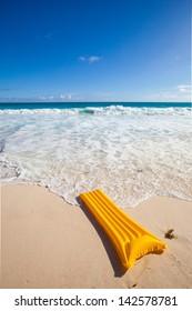 yellow air mattress at the beach near the waves of the sea