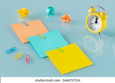 A yellow alarm clock, along with colorful, blank note cards.  Colorful office staples, washed out paper balls, Space for an inscription, Concept