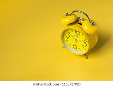 Yellow alarm Clock analog classic retro style on yellow background and copy space.