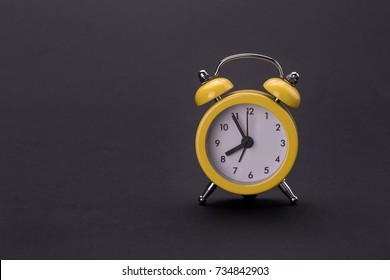 yellow alarm clock on a balck background