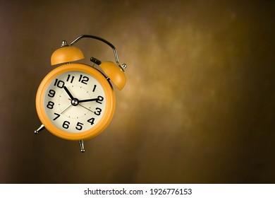 Yellow alarm clock on vintage background