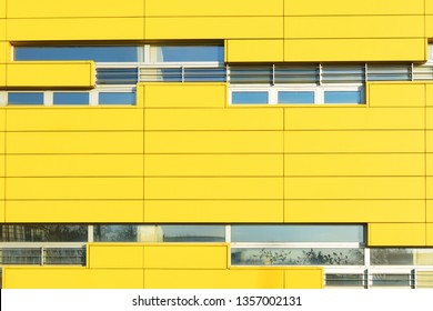 Yellow aluminum composite panel wall  with white windows. It is the wall of the office building that belongs to a Serbian post office.