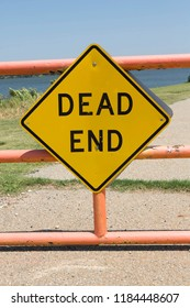 A yellow American Dead End sign attached to a gate.