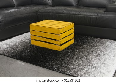 Yellow apple box as a coffee table on modern design home interior rug