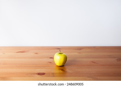 yellow apple isolated on a wooden board