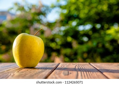 Yellow Apple lying on a brown wooden background