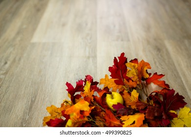 Yellow apple with red fall leaves on wooden floor