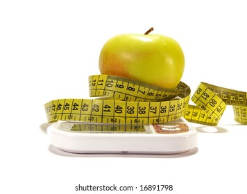 Yellow apple, scale and tape measure isolared