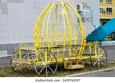 yellow arbor in the form of a carriage welded from steel gratings and benches inside it