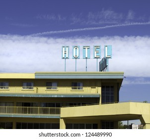 Yellow architecture and turquoise sign on an old hotel.