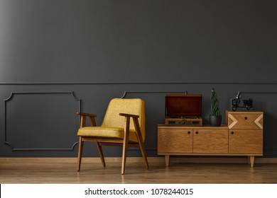 Yellow armchair and retro cabinet with a record player and a plant on the grey wall in dark living room interior