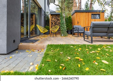 Yellow armchairs and grey sofas in the garden of single family home