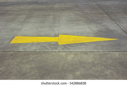 Yellow arrow crosswalk on asphalt in car park.