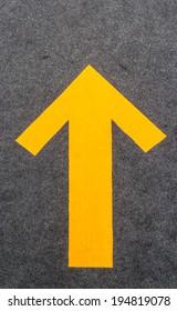 yellow arrow on the gray carpet, pathway.