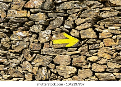 Yellow arrow on the old wall, direction indicator on the pilgrim routes The Way of Saint James(El Camino de Santiago).
