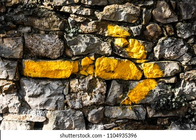 Yellow arrow painted on stone wall on the way to Santiago de Compostela