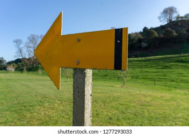 Yellow Arrow Pointing Left With Green Grass Background