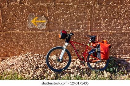 Yellow arrow sign and bicycle of Camino de Santiago way of Saint James pilgrims