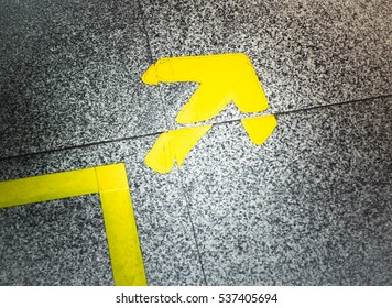 Yellow arrow sign indicate on marble floor, On the subway
