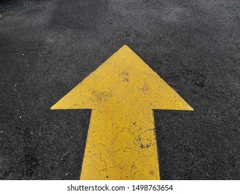 Yellow arrow sign pointing forward on an asphalt road. concept of business,travel and destinations