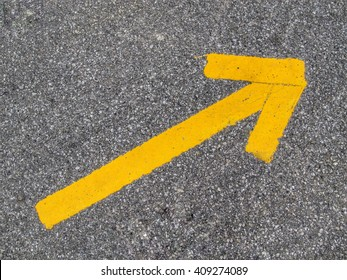 yellow arrow sign or symbol on the asphalt background  texture