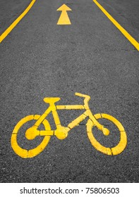 yellow arrows and bicycle sign path on the road